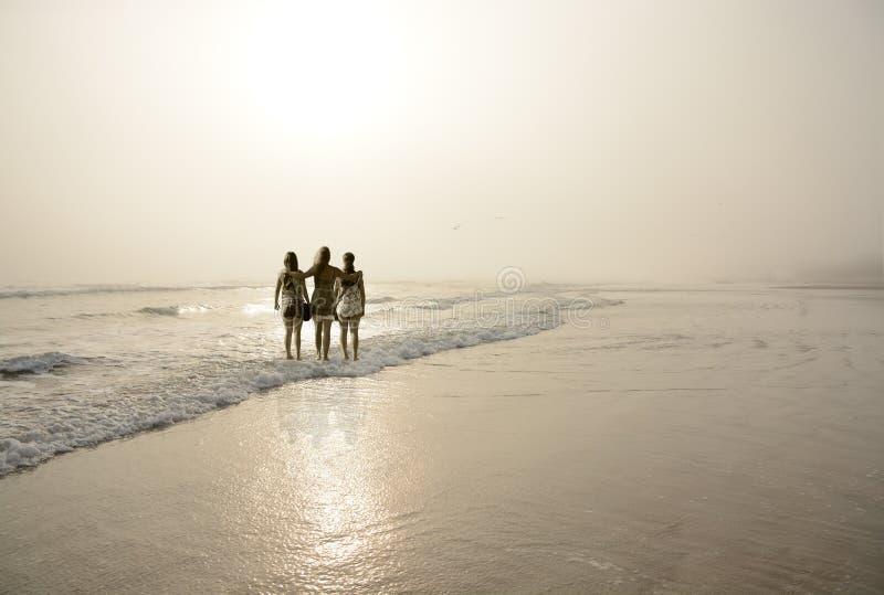 一起享受时间的母亲和女儿在一个有雾的海滩 免版税图库摄影