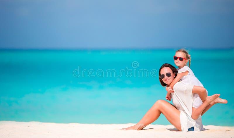 一起享受时间的母亲和女儿在热带海滩 库存照片