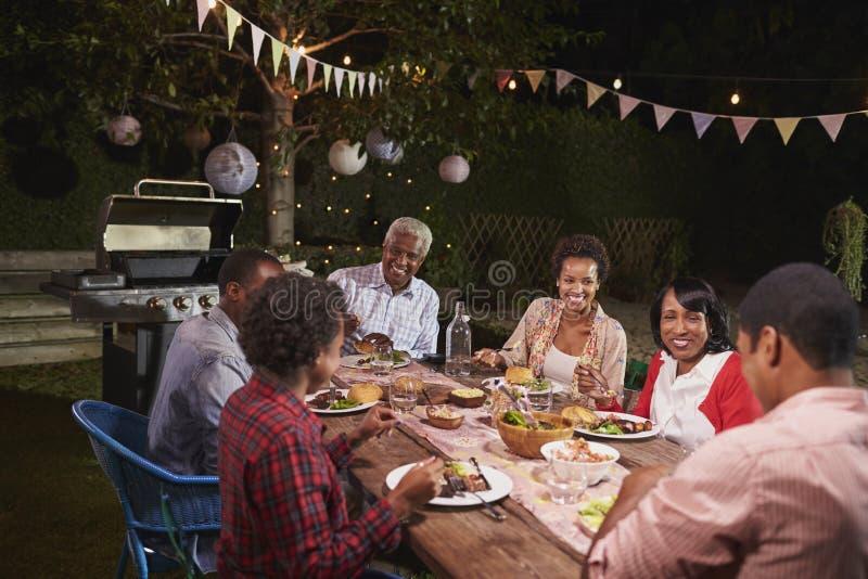 一起享受晚餐的成人黑家庭在他们的庭院里 库存照片