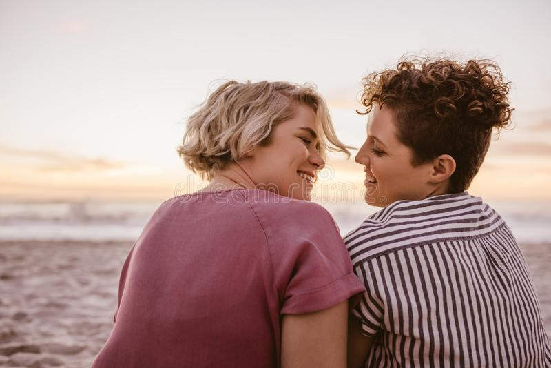 一起享受浪漫海滩日落的微笑的年轻女同性恋的夫妇 免版税图库摄影