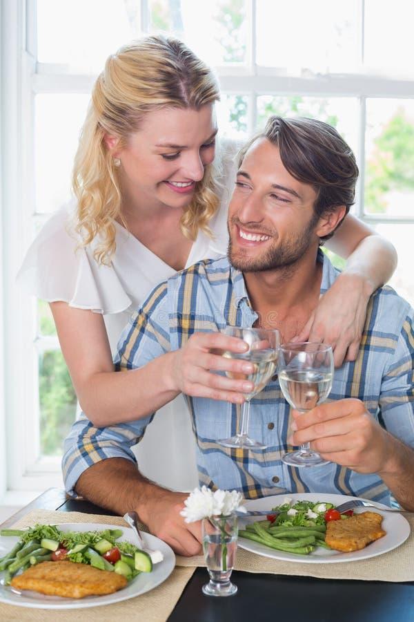 一起享受膳食的逗人喜爱的微笑的夫妇 库存图片