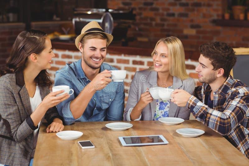 一起享用咖啡的微笑的朋友 库存图片