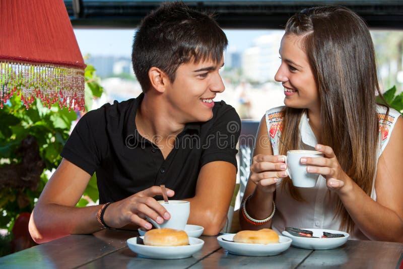 一起享用咖啡的青少年的夫妇。 免版税库存照片