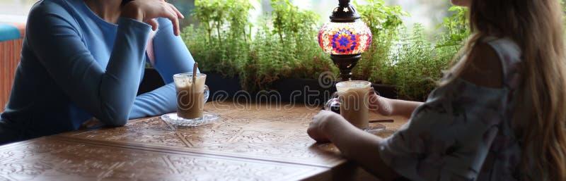 一起享用在咖啡馆的女朋友 见面在咖啡馆的少妇 遇见一个咖啡馆的两名妇女咖啡的 蓝色礼服,礼服 免版税库存图片
