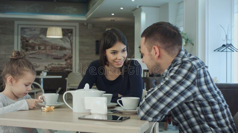 一起享用在咖啡馆的家庭茶 谈话的父母看他们的女儿 免版税库存图片