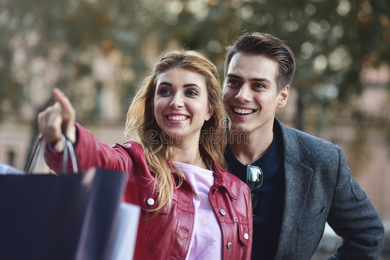 一起享用在购物的美好的年轻夫妇,获得乐趣 消费者至上主义,爱,约会,生活方式概念 免版税库存照片