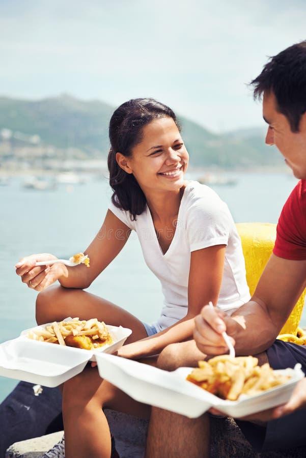 一起享用有些炸鱼加炸土豆片在港口 免版税库存照片