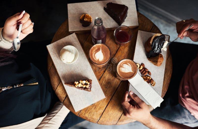 一起享用点心和咖啡的朋友在咖啡馆 免版税库存照片