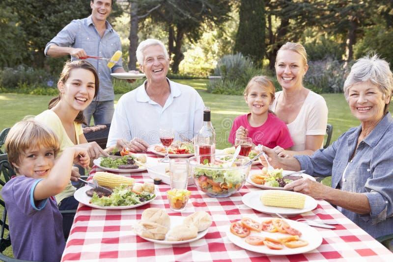 一起享用烤肉的三一代家庭在庭院里 免版税库存照片