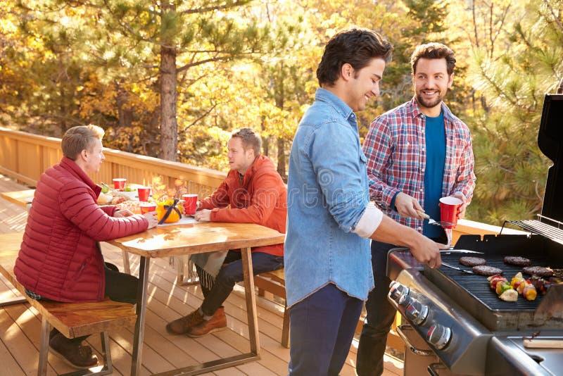 一起享用烤肉的小组快乐男性朋友 免版税库存图片
