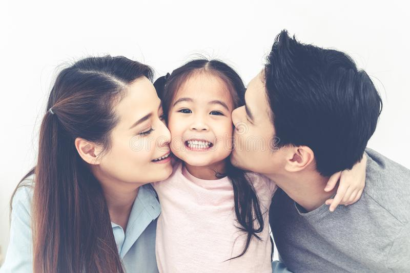 一起亲吻女儿的面颊的可爱的亚裔爸爸和妈妈画象接近在被隔绝的白色演播室背景 免版税库存图片