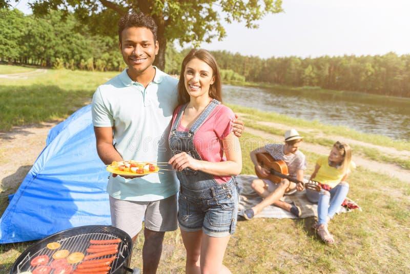 一起休息在森林里的快乐的朋友 免版税库存图片