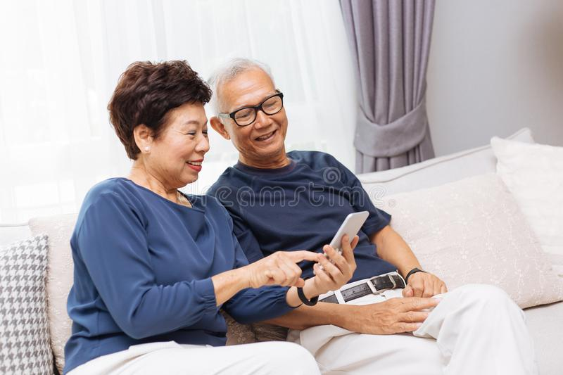 一起使用一个巧妙的电话的资深亚裔夫妇祖父母在沙发在家 免版税库存照片