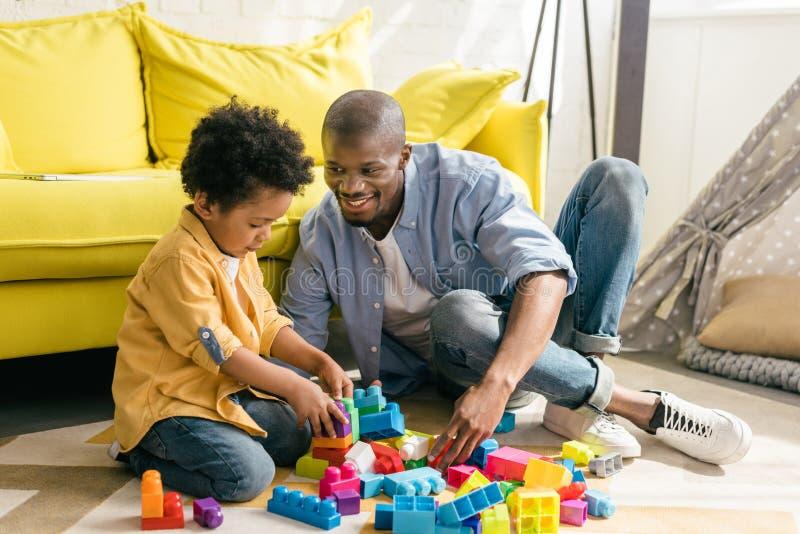 一起使用与五颜六色的块的微笑的非裔美国人的父亲和小儿子 免版税库存照片