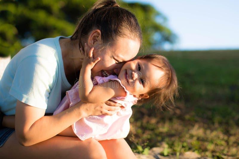 一起使用和笑在公园的母亲和女儿 图库摄影