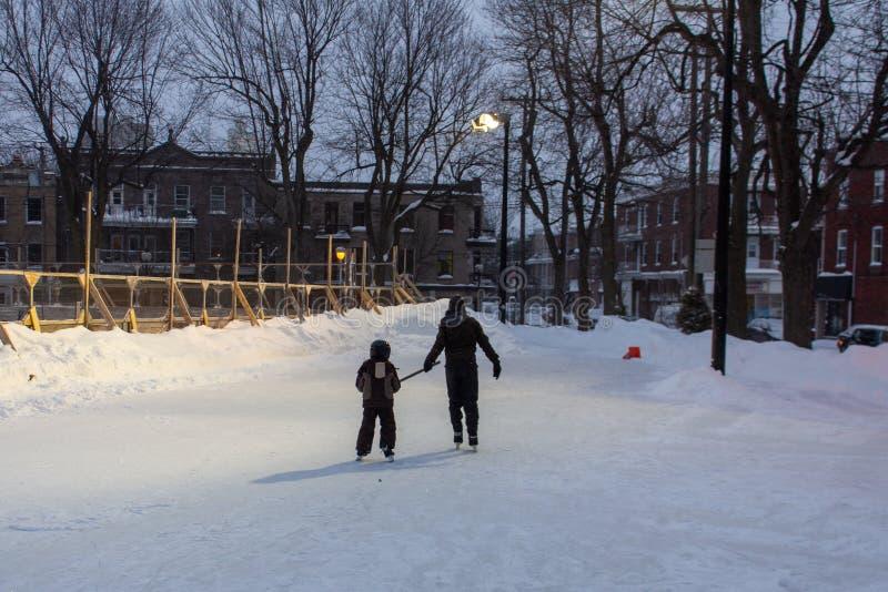 一起使用在冰鞋的孩子和年轻成人,当在一个溜冰场在一个公园- 1/2时 免版税库存照片