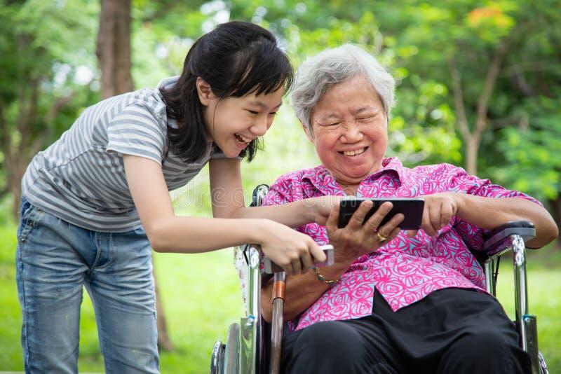 一起使用手机的愉快的亚裔资深祖母和小孩女孩,打在智能手机的电子游戏,微笑的老人 图库摄影