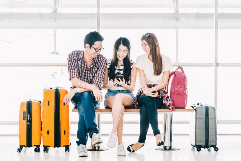 一起使用智能手机检验飞行或网上报到的小组年轻亚裔旅客在机场 库存图片