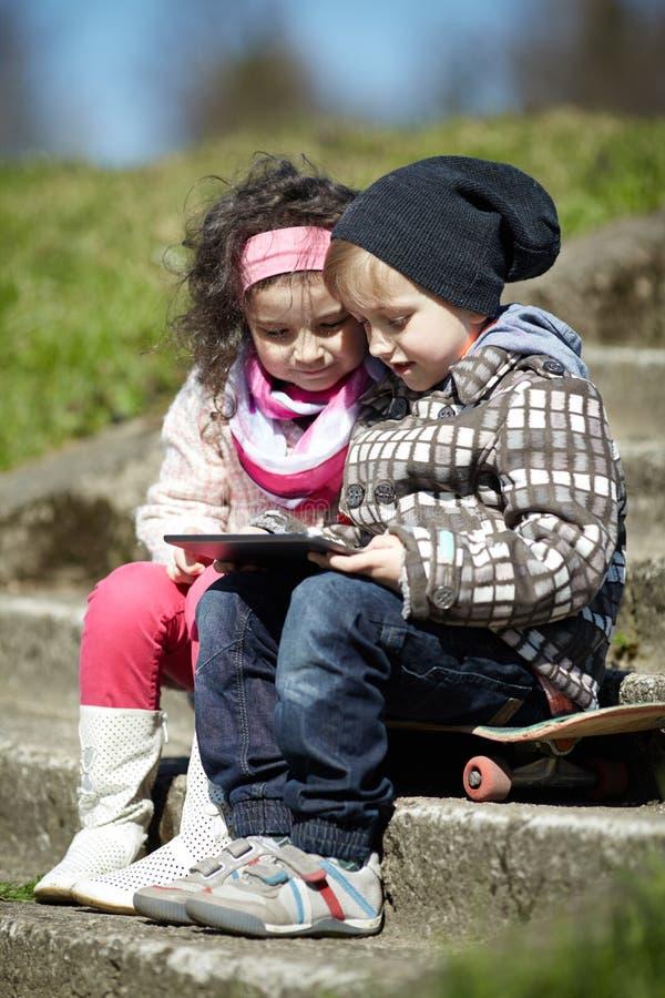一起使用片剂的男孩和女孩 免版税库存图片