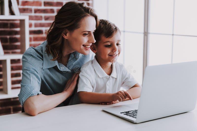 一起使用膝上型计算机的母亲和儿子在家 库存照片
