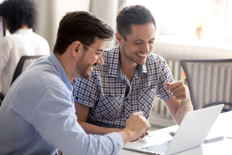 一起使用膝上型计算机的男性同事,获得乐趣在工作 免版税库存图片