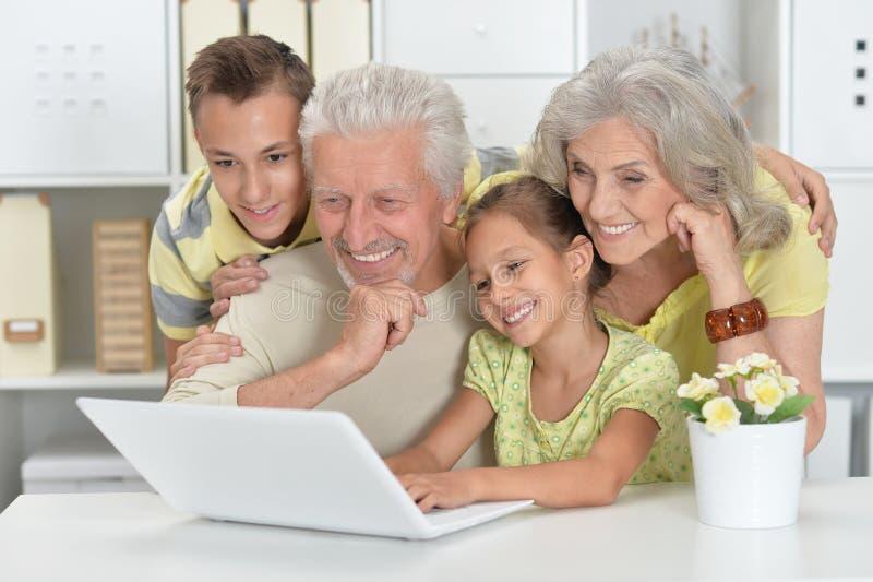 一起使用膝上型计算机的祖父母和孙 免版税库存图片