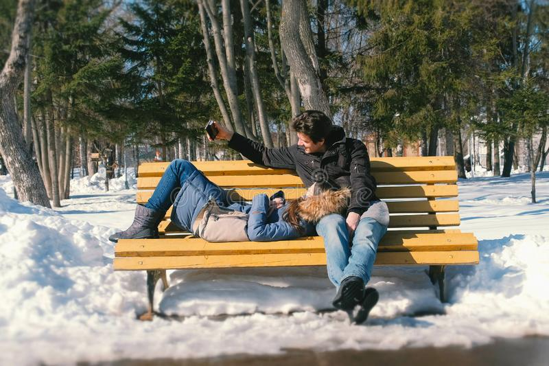 一起供以人员和妇女休息在一条长凳在冬天城市公园 晴朗的冬日 人在电话做selfie 免版税库存照片