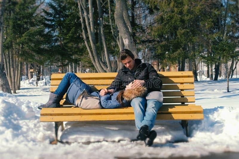 一起供以人员和妇女休息在一条长凳在冬天城市公园 晴朗的冬日 图库摄影