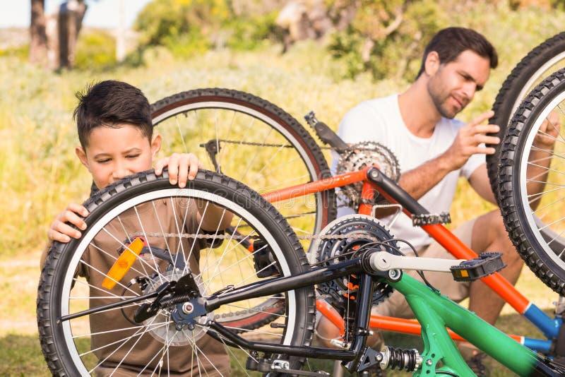 一起修理自行车的父亲和儿子 库存图片