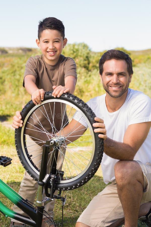一起修理自行车的父亲和儿子 库存照片