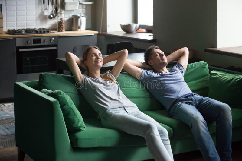 一起倾斜在沙发的愉快的夫妇,注重自由周末conce 库存图片
