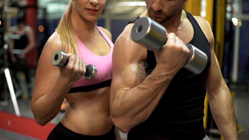 一起做哑铃举的锻炼的少妇和教练员在健身房,健康 免版税库存图片