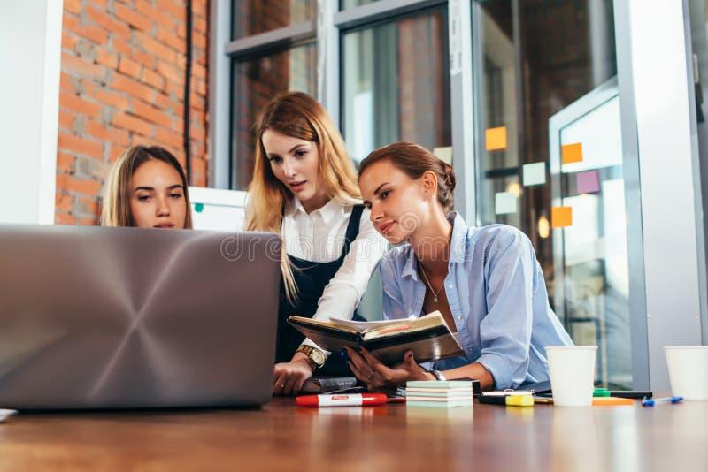 一起做家庭作业的三位女性大学生使用一台膝上型计算机和坐在书桌的演讲笔记在书房 免版税库存照片