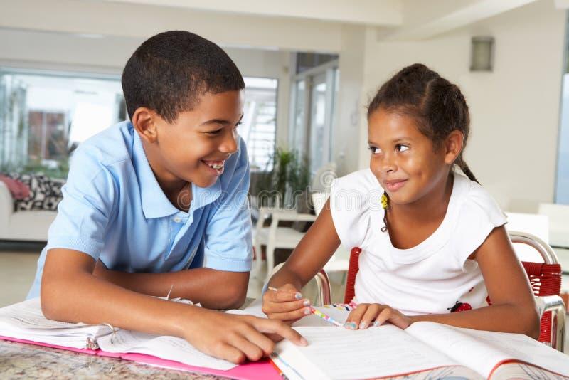 一起做家庭作业的两个孩子在厨房里 免版税库存照片
