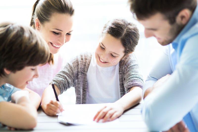 一起做家庭作业的家庭在桌上 免版税库存照片
