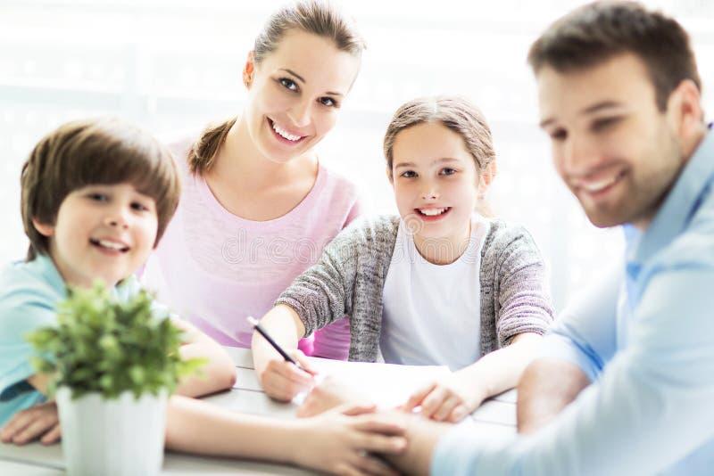 一起做家庭作业的家庭在桌上 图库摄影