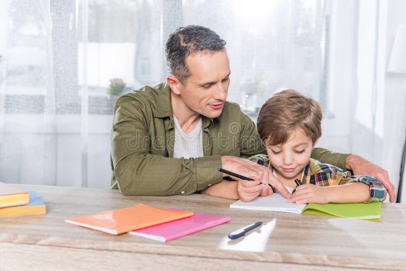 一起做家庭作业的父亲和可爱的儿子 免版税库存图片