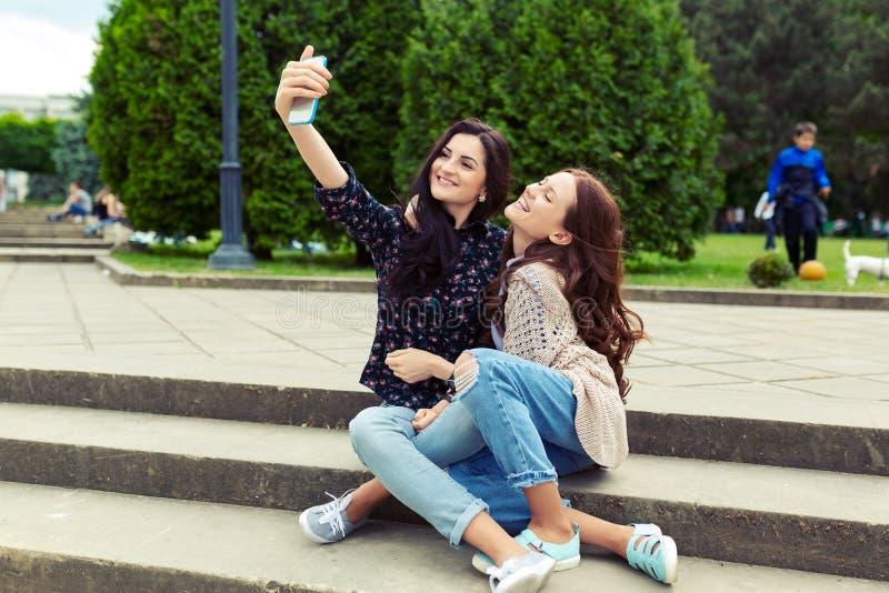 一起做滑稽的selfie的两个女孩在街道,获得乐趣 免版税图库摄影