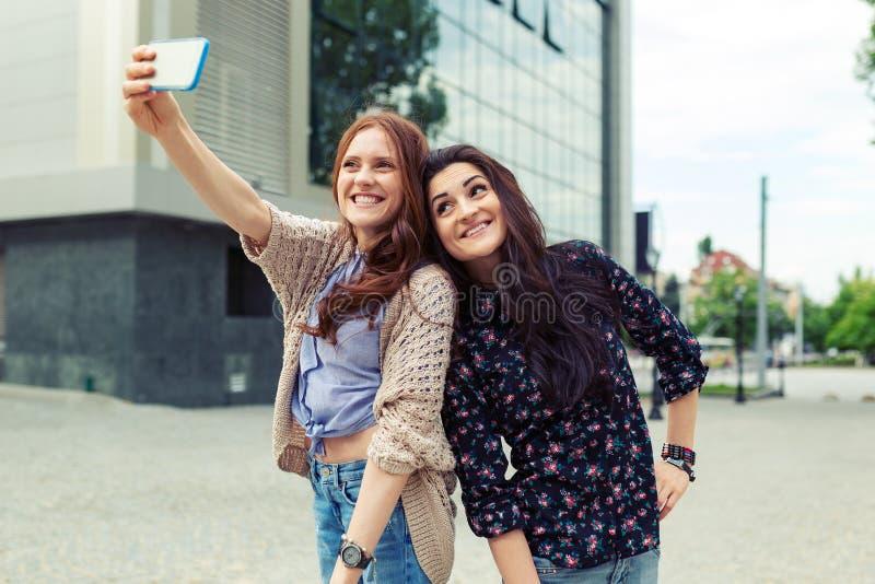 一起做滑稽的selfie的两个女孩在街道,获得乐趣 图库摄影