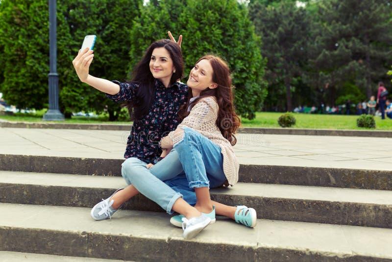 一起做滑稽的selfie的两个女孩在街道,获得乐趣 库存照片