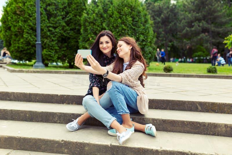 一起做滑稽的selfie的两个女孩在街道,获得乐趣 库存图片