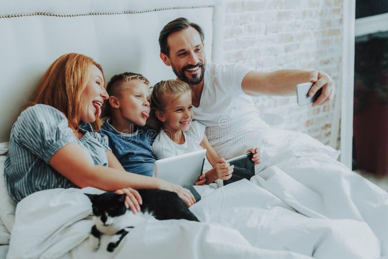 一起做滑稽的selfie的家庭在床上 库存图片
