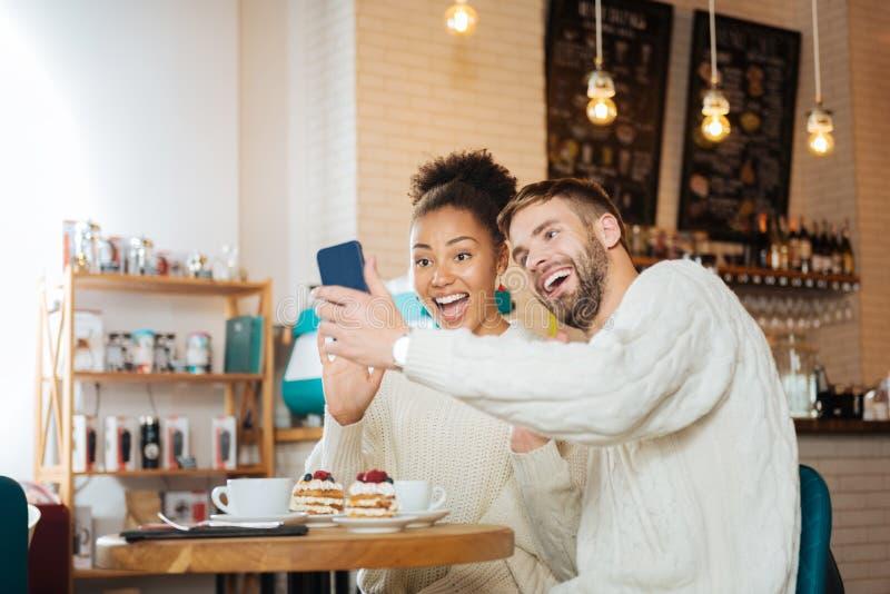 一起做滑稽的selfie的放光的年轻夫妇 库存照片