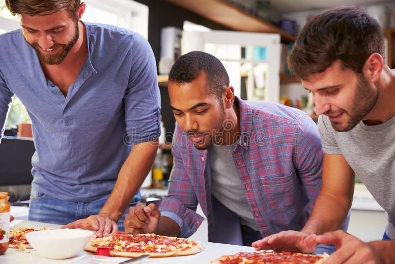 一起做薄饼的三个男性朋友在厨房里 免版税图库摄影