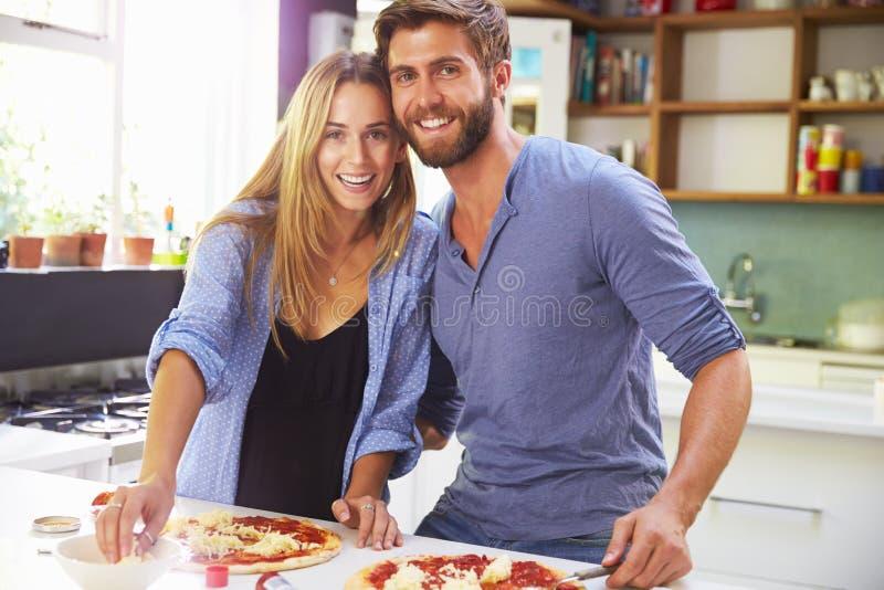 一起做薄饼的年轻夫妇在厨房里 免版税库存照片