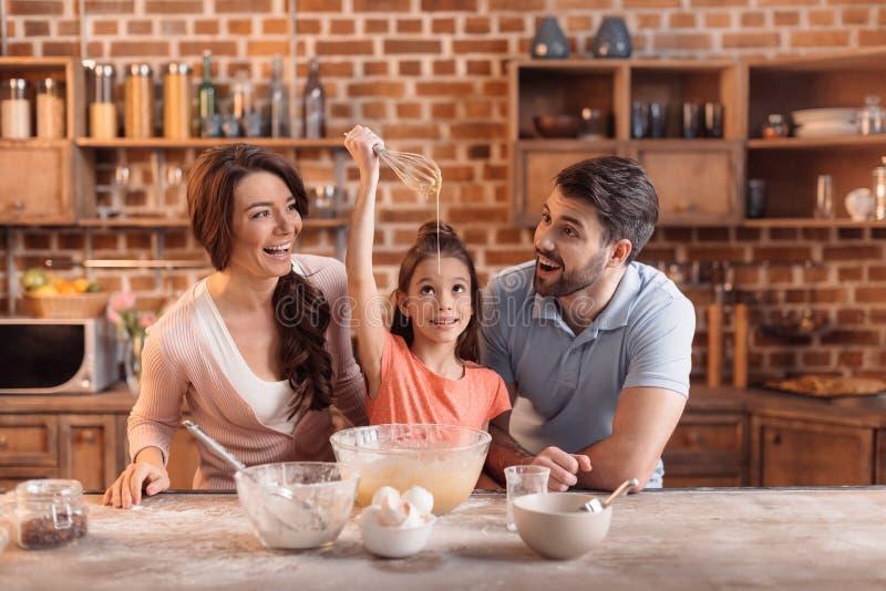 一起做蛋糕的愉快的家庭在厨房里 库存图片