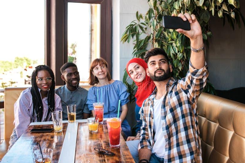 一起做selfie的小组愉快的朋友在智能手机在咖啡馆 库存图片