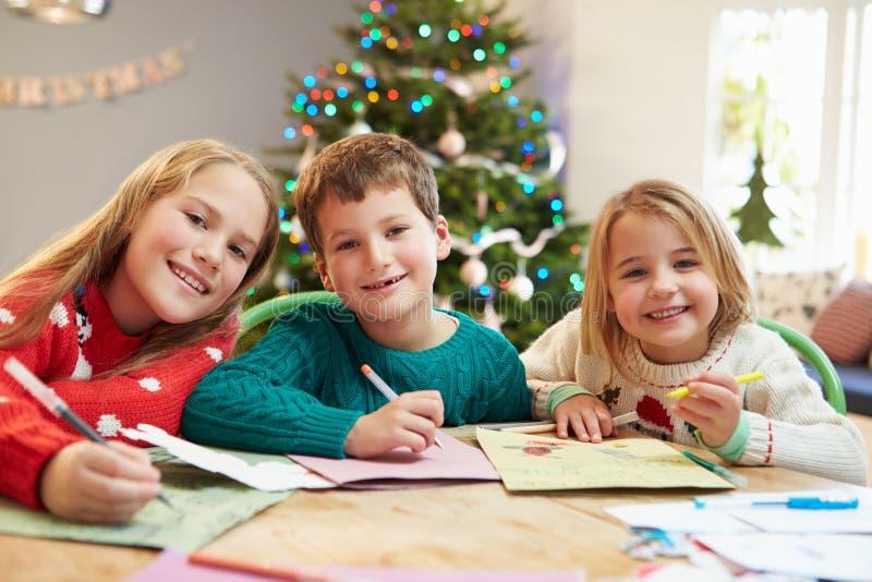 一起写信的三个孩子给圣诞老人 免版税库存照片