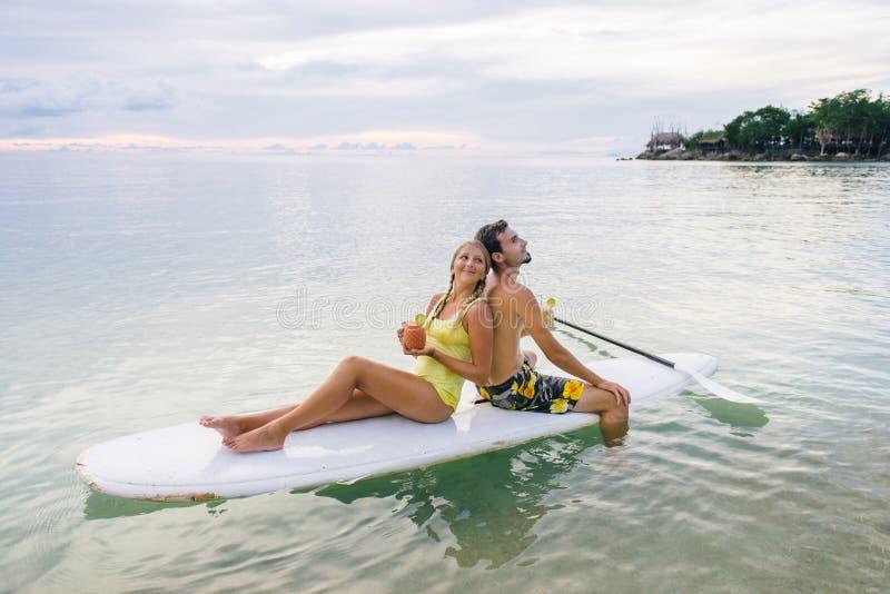 一起冲浪在明轮轮叶的愉快的夫妇在日落 免版税库存照片