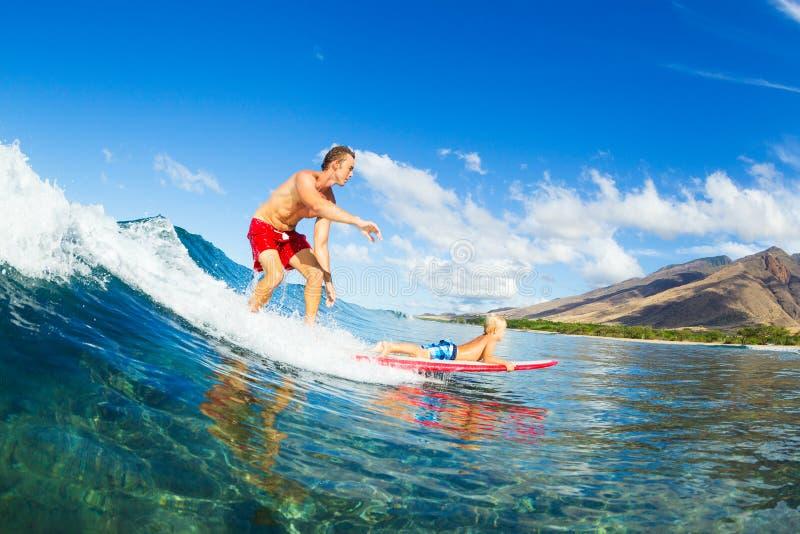 一起冲浪的父亲和的儿子,乘坐的波浪 图库摄影